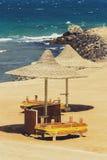 Einsamer Strand mit geflochten Sonnenschirmen lizenzfreie stockfotos