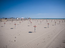 Einsamer Strand mit nur den Unterstützungen verwendete, um den Sonnenschirm zu sichern Lizenzfreie Stockfotos