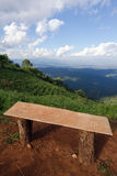 Einsamer Stuhl mit Ansicht des Grases, des Berges und des bewölkten Himmels von Chiangm stockfotografie