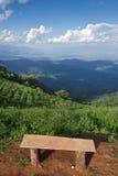Einsamer Stuhl mit Ansicht des Grases, des Berges und des bewölkten Himmels von Chiangm Lizenzfreies Stockbild