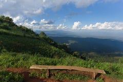 Einsamer Stuhl mit Ansicht des Grases, des Berges und des bewölkten Himmels von Chiangmai Lizenzfreie Stockfotografie
