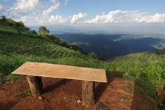 Einsamer Stuhl mit Ansicht des Grases, des Berges und des bewölkten Himmels von Chiangmai Thailand Stockbild