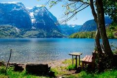 Einsamer Stuhl nahe See- und Naturhintergrund Lizenzfreie Stockfotografie