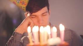 Einsamer trauriger Junge des Porträts, der vor wenigem Kuchen mit den brennenden Kerzen schauend auf ihm sitzt Unglücklicher Mann stock video footage