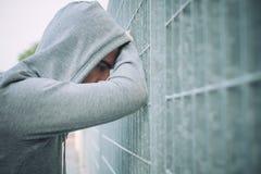 Einsamer und deprimierter Mann, der an einem Zaun sich lehnt Stockfotos