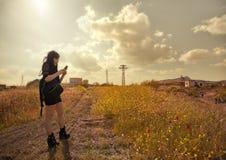 Einsamer verlorener Brunette, der ihr Telefon in der Landschaft aufpasst lizenzfreies stockbild