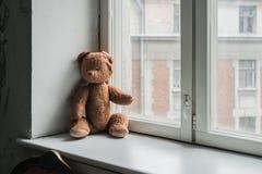 Einsamer Weinleseteddybär betreffen das Fenster Stockbild