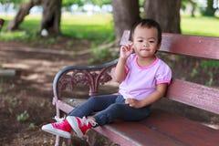 Einsames asiatisches Baby, das auf Bank sitzt Lizenzfreie Stockbilder