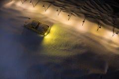 Einsames Autofahren auf eine Schnee bedeckte Straße mit Straßenlaternen im Schneewetter nachts Grafikdekoration für Grußkarte neu lizenzfreies stockbild