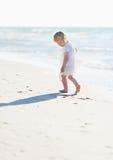 Einsames Baby, das auf Seeufer spielt Stockbilder