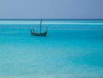 Einsames Boot auf blauem Meer Stockfoto