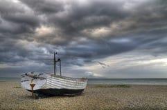 Einsames Boot auf Strand unter einem stürmischen Himmel Stockfoto
