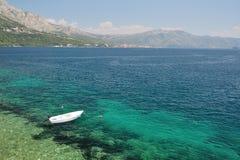 Einsames Boot, das allein auf Strand von Korcula, Kroatien schwimmt Lizenzfreies Stockbild