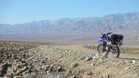 Einsames Doppelsportmotorrad auf leerem Schotterweg in Death- Valleywüste in Vereinigten Staaten Stockfotografie