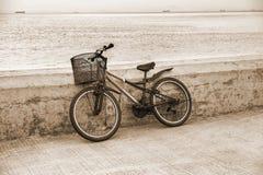 Einsames Fahrrad, das auf konkretem Pier steht stockbild