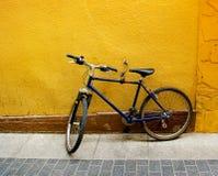 Einsames Fahrrad an einer gelben Wand Lizenzfreies Stockfoto
