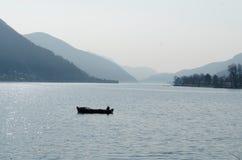 Einsames fisheing Boot auf einem See von Lugano, die Schweiz, mit Bergen Stockbilder