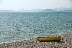 Einsames gelbes Boot an der Küste Lizenzfreies Stockbild