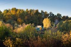 Einsames Häuschen im Wald gegen den Hintergrund des Herbstbaums Lizenzfreies Stockbild