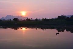 Einsames hölzernes Boot, das im Fluss bei dem Sonnenuntergang, Myanma sich reflektiert Stockbild