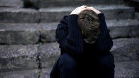 Einsames Jungenschreien, sitzend auf alten gebrochenen Schritten, erschrockenes Kriegskind, Obdachloser lizenzfreie stockfotos