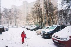 Einsames Kind, das in Schnee geht Lizenzfreie Stockfotos