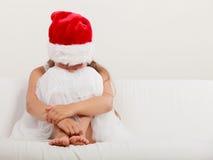 Einsames Kind des kleinen Mädchens in Sankt-Hut Weihnachten Stockfoto