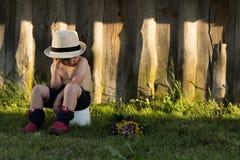 Einsames Kind mit Blumen Seashells gestalten auf Sandhintergrund lizenzfreie stockbilder