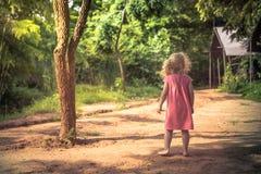 Einsames Kindermädchen, das barfuß allein auf ländlicher Landschaftsstraße unter Bäumen im Park steht und das Abstandskonzept chi lizenzfreies stockfoto
