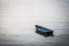 Einsames kleines Boot, das auf den See schwimmt lizenzfreies stockfoto