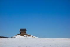 Einsames kleines Gebäude auf kleinem Felshügel im Winter Stockbilder