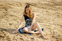 Einsames lächelndes Mädchen, das auf dem sonnigen Meersandstrand sich entspannt Stockfotografie