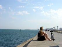 Einsames Mädchen auf der Küstenlinie Stockbilder