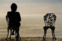 Einsames Mädchen auf einem Stuhl Stockfoto