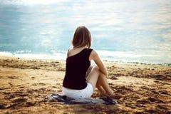 Einsames Mädchen, das auf dem Seestrand sich entspannt Lizenzfreie Stockbilder