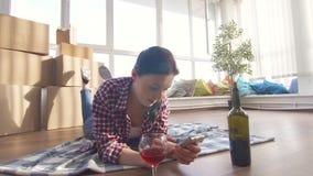 Einsames Mädchen, das auf dem trinkenden Wein des Bodens liegt und einen Smartphone verwendet stock video