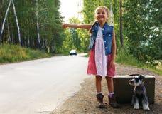 Einsames Mädchen, das auf der Straße mit einem Koffer und einem Hund, rais steht Lizenzfreies Stockbild