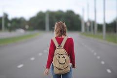 Einsames Mädchen, das auf der Straße mit einem Rucksack per Anhalter fährt stockbilder