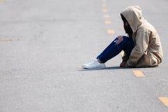 Einsames Mädchen, das auf der Straße sitzt lizenzfreie stockfotografie