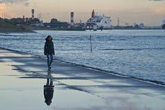 Einsames Mädchen, das auf einen nass Pier im Hoek van Holland geht stockfotografie