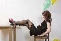 Einsames Mädchen, das auf Stuhl im leeren Raum sitzt Lizenzfreie Stockfotos