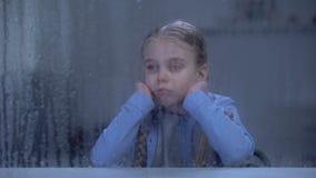 Einsames Mädchen, das Fenster im regnerischen Wetter, Warteeltern von der Arbeit betrachtet stock video footage