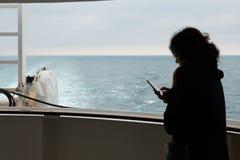 Einsames Mädchen mit einem Smartphone auf der Plattform eines Kreuzschiffs im Ozean lizenzfreies stockbild