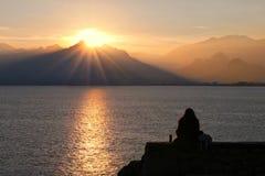 Einsames Mädchen passt Sonnenuntergang auf lizenzfreies stockfoto