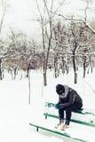 Einsames Mädchen steht im schneebedeckten Stadtpark des Winters Stockfoto