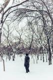 Einsames Mädchen steht im schneebedeckten Stadtpark des Winters Stockfotografie