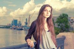Einsames Mädchenwarten Ihr Hellgraues Hemd tragend, schwärzen Sie Jacke, einen bereitstehenden Zaun der jungen amerikanischen Fra Lizenzfreie Stockfotos