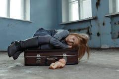Einsames Mädchen, das auf dem Koffer sitzt Lizenzfreie Stockfotografie