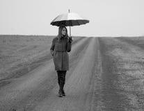 Einsames Mädchen mit Regenschirm an der Landstraße. Stockfotos