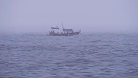 Einsames Motorboot mit Touristen oder Fischern in der hohen See im bewölkten nebeligen Wetter stock footage